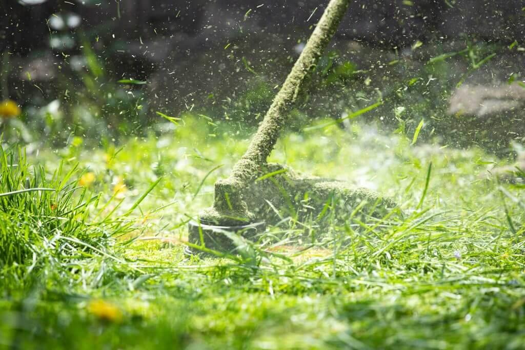 a-lawn-mower-is-cutting-green-grass-H88UTTK