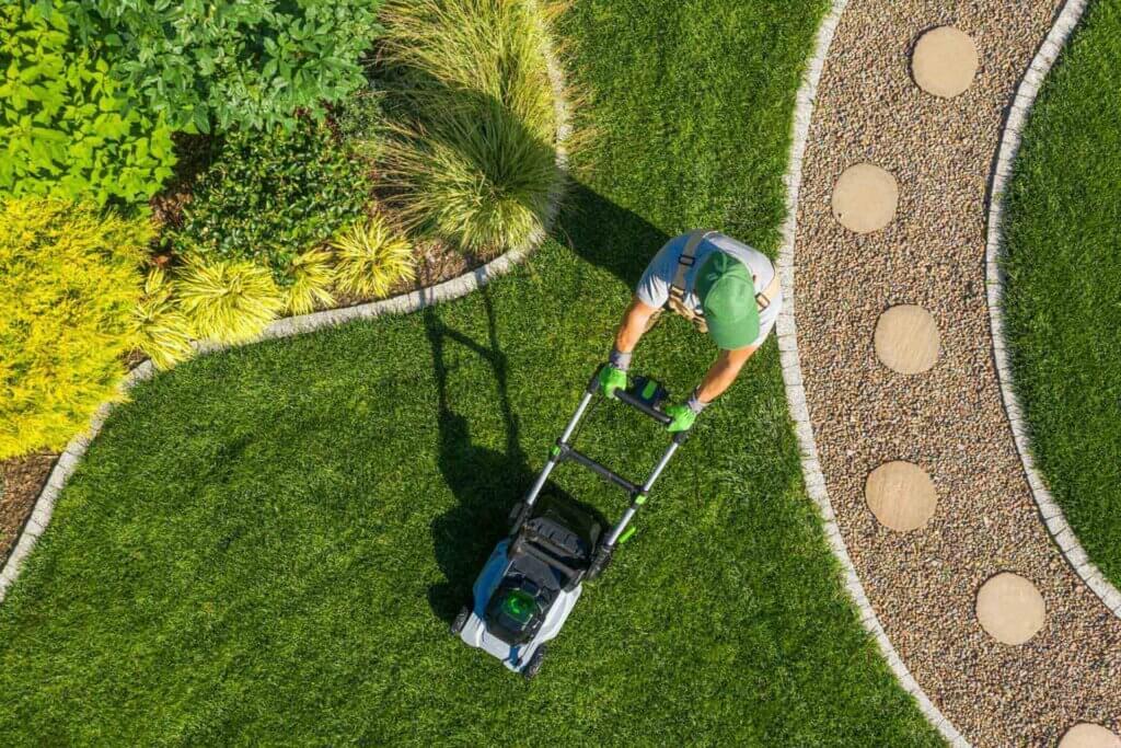 gardener-mowing-backyard-garden-grass-aerial-view-46KSDUZ